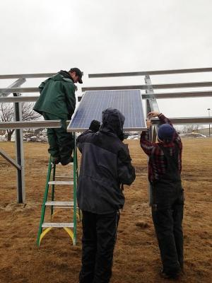Crews work to install solar arrays at the Cherryland Electric Cooperative facility off U.S. 31 near Grawn. Co-op members can opt to buy a solar panel in the array at a cost of $470 per panel. The community-based initiative helps lower the cost barrier for people to adopt solar energy.