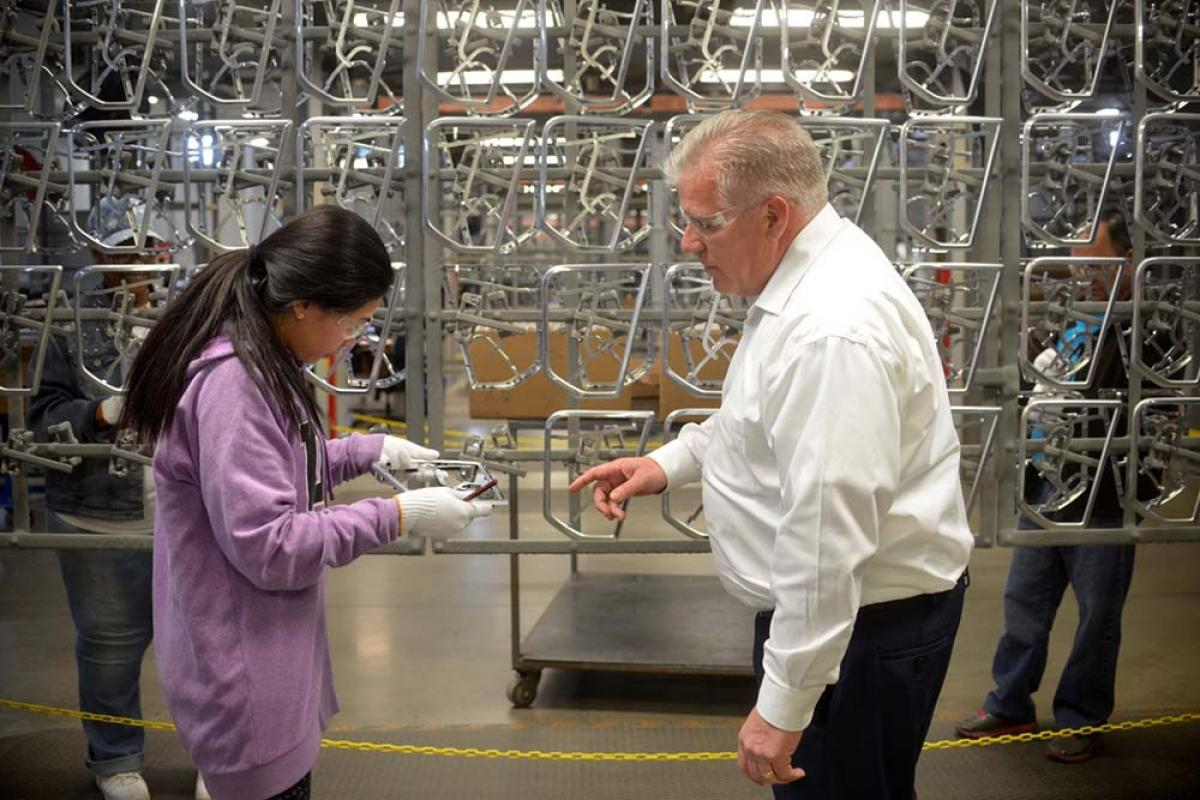 Nick Hrnyak, president of Lack Enterprises, looks on as a worker inspects an electroplated part. The company for years was mandated by the EPA to use a PFOS- based vapor suppressant to curb chromium air emissions in its plating process. Now, the company and other platers are being held accountable for contamination caused by the chemical at former facilities and in wastewater discharges.