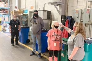 A screener takes the temperature of workers before they start their shifts at Cascade Engineering in Grand Rapids.