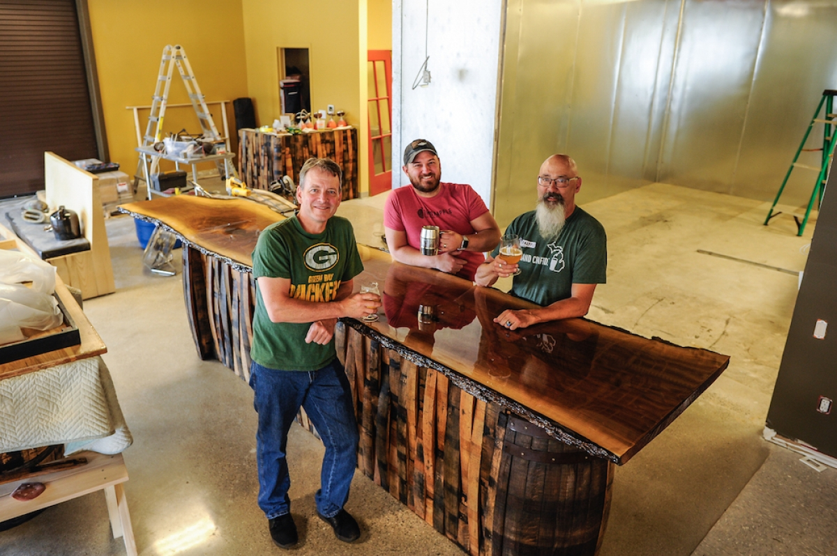 Thornapple Brewing Co. co-founder Jeff Coffey, left, brewer Sebastian Henao, center, and co-founder Eric Fouch, right, show off the bar and cooler space where the Cascade Township brewery will expand. A grand re-opening is planned for June 15, coinciding with the company's second anniversary.