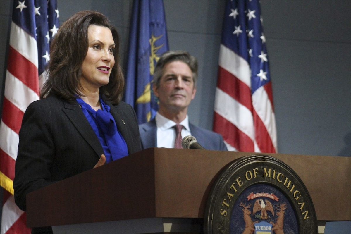 Gov. Gretchen Whitmer speaks at a press conference today while DTE Energy Executive Chairman Gerry Anderson looks on.