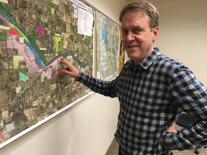 John Scholtz, Ottawa County's parks and recreation director, points to a map outlining the expanding Grand River Greenway, which will create a 26.3-mile network of trails along the Grand River that will extend from Jenison to Grand Haven.