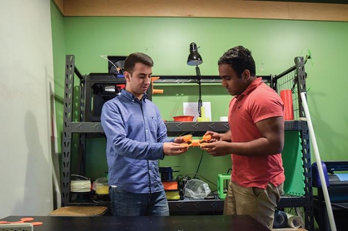 While drones currently on the market have exposed rotors, Mario Swaidan, left, designed AerBots with enclosed rotors to make it safer for students to use. Although his first prototype was made from wood purchased at a Jo-Ann Fabrics and Crafts store, Swaidan's finished product will be made from injection-molded plastic.
