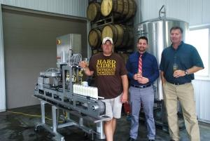 New semi-automatic canning equipment designed by Belmont-based Microcanner offers Sietsema Cider a scalable solution for packaging its products at its farm-based cider mill and tasting room at 8540 2 Mile Road NE in Ada. Pictured (l-r) are Andy Sietsema of Sietsema Cider; Eric Finnigan of The Wirt-Rivette Group, the firm that provided the equipment financing; and Todd Vriesenga of Microcanner LLC.