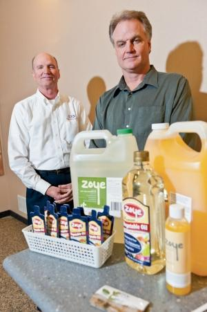 Brothers Cliff, left, and Robb Meeuwsen, right, show off some of Zeeland Farm Services' soybean oil products, sold under the Zoye name.
