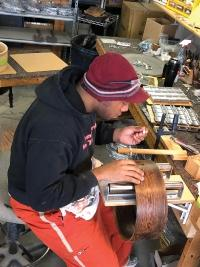 Production Manager Jamel Taylor puts a sterling silver inlay into a drum shell at Black Swamp Percussion in Zeeland.