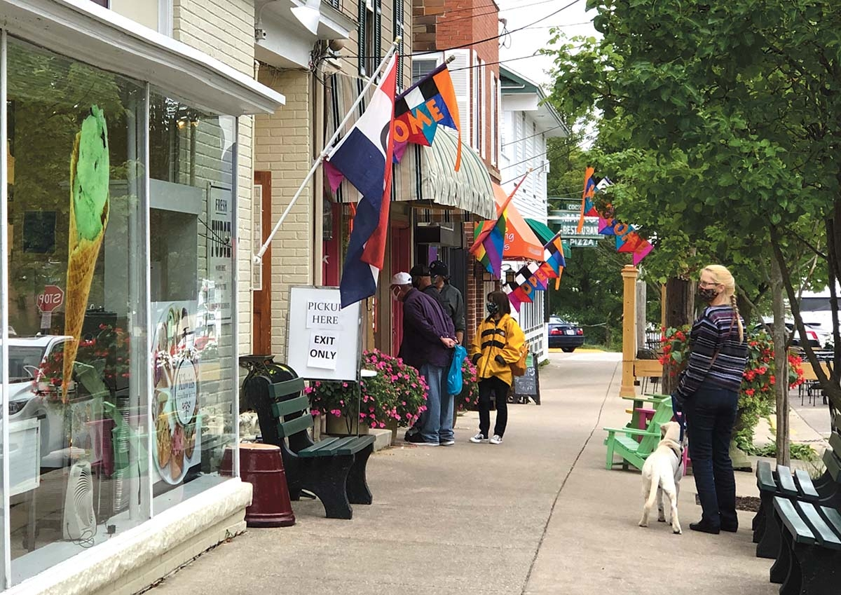 Shoppers peer into a downtown storefront on Sept. 9 on Mason Street in Saugatuck.